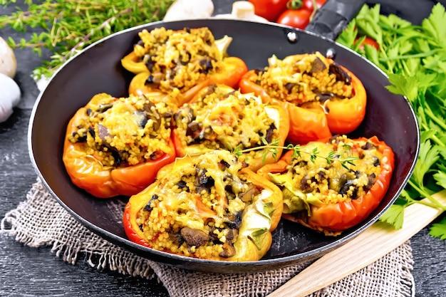 버섯, 토마토, 쿠스쿠스, 치즈로 속을 채운 달콤한 고추는 삼베, 포크, 마늘, 파슬리, 백리향을 나무 판자를 배경으로 한 오래된 프라이팬에 넣습니다.