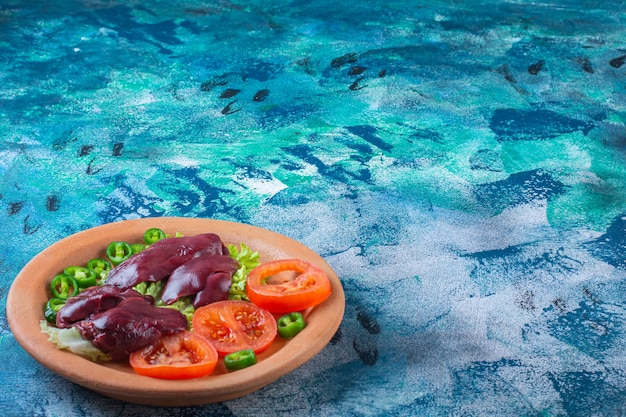 Перец, помидоры, листья салата и куриные субпродукты на глиняной тарелке