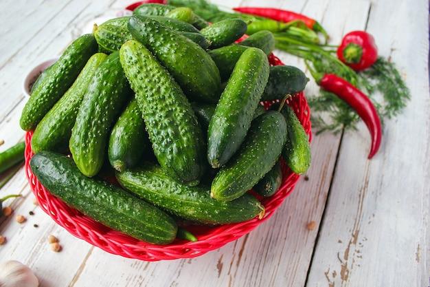 緑と赤と唐辛子、フェンネル、塩、黒胡pepper、ニンニク、エンドウ豆と白い木製テーブルの上の赤いバスケットに新鮮な有機キュウリ、クローズアップ、健康概念、平面図、フラットレイアウト