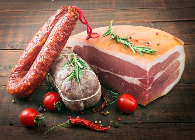 おいしいスモークソーセージ(サラミ)胡pepper、トマト、ローズマリー、木の板