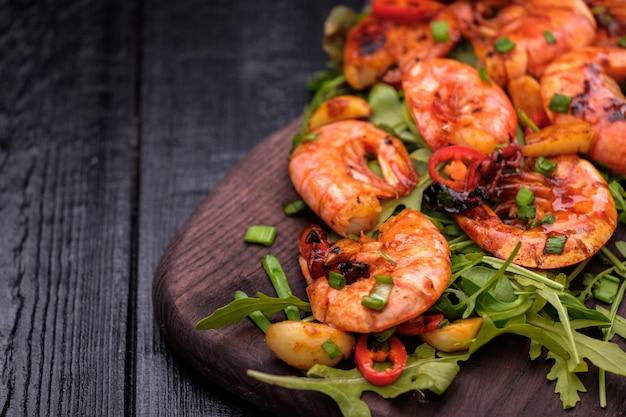 海老フライ、胡pepper、ニンニク、レモン添え。地中海料理。アジア料理。