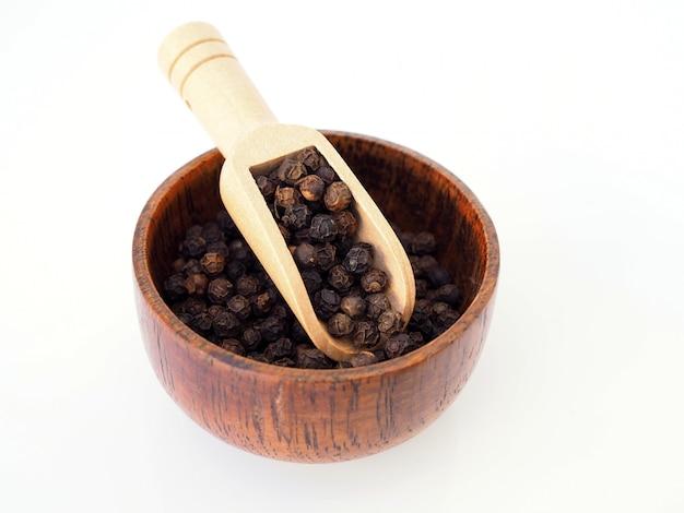 白い表面に分離された木製のボウルに黒胡pepperの種。
