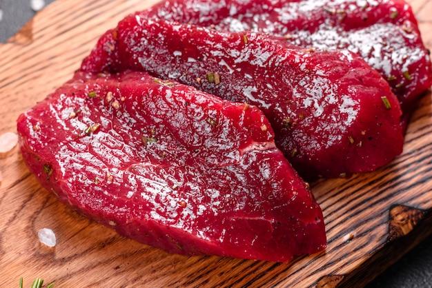 新鮮な生の牛肉ステーキミニョン、塩、胡pepper、タイム、トマト添え。生の新鮮な霜降り肉ステーキと調味料