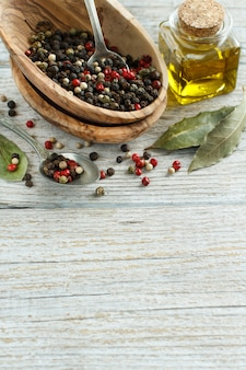 Peppercorn mix in a bowl, bay leaves  and olive oil on a wooden table