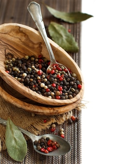 スプーンと月桂樹の葉を入れたボウルにコショウの実を混ぜる