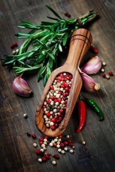 Смесь перца в деревянной ложке, зелень и специи