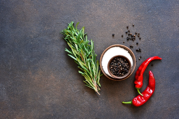 Peppercorns, chili and fresh rosemary on a concrete background.