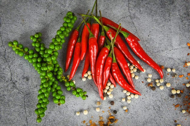 Peppercorns and fresh red chilli on dark , fresh green peppercorn and pepper seed for ingredients cuisine thai food herbs and spices