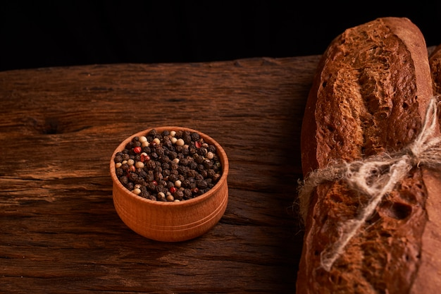 Peppercorns in a wooden bowl on table with food rustic style