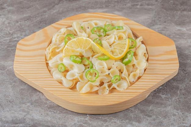 Паста фарфалле с перцем и ломтиком лимона на деревянной тарелке, на мраморе.