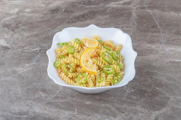 Паста фузилли с перцем и ломтиком лимона на деревянной тарелке, на мраморной поверхности.