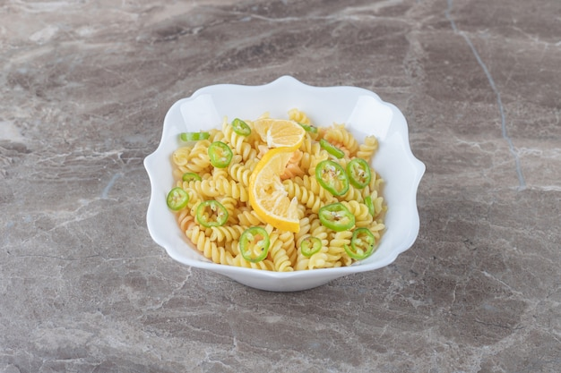 Peppered fusilli pasta with lemon slice on wooden plate , on the marble surface.