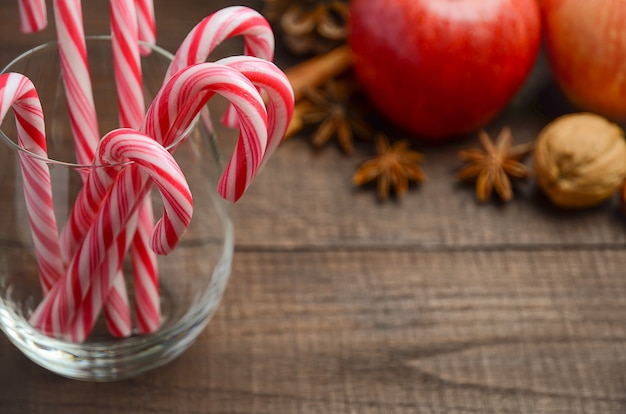 Peppermint candy canes and other christmas decorations on wooden background