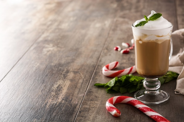 Peppermint coffee mocha for christmas on wooden table copy space
