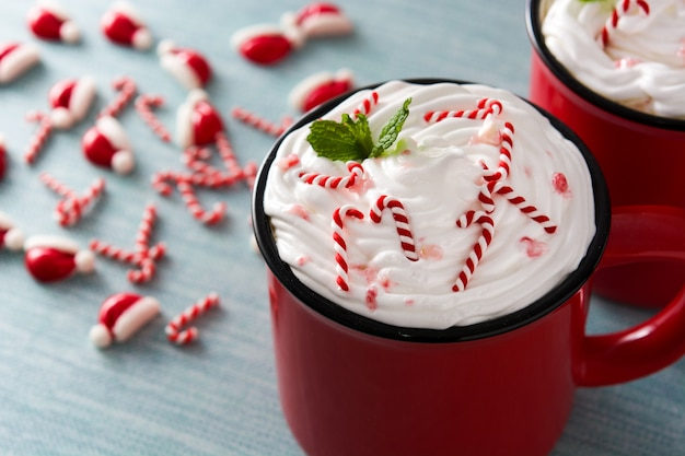 Peppermint coffee mocha decorated with candy canes for christmas on blue background