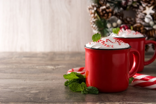 Peppermint coffee mocha decorated with candy canes for christmas on wooden table copyspace