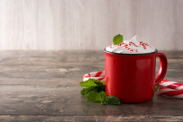 Peppermint coffee mocha decorated with candy canes for christmas on wooden table