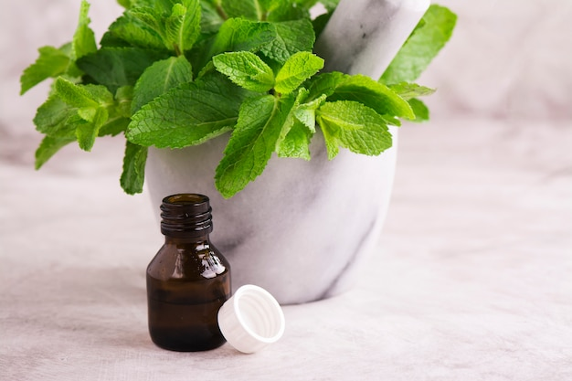 Peppermint oil and fresh mint leaves over wooden table
