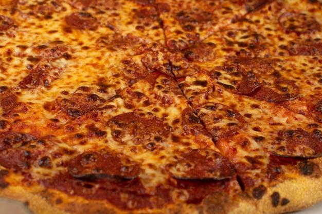 Pepperoni or diabola pizza texture background with salami, chili pepper and mozzarella cheese. traditional italian flatbread