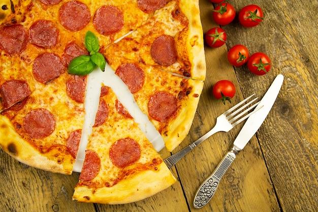 古い木製のテーブル、フォークとナイフ、上面図のペパロニピザ