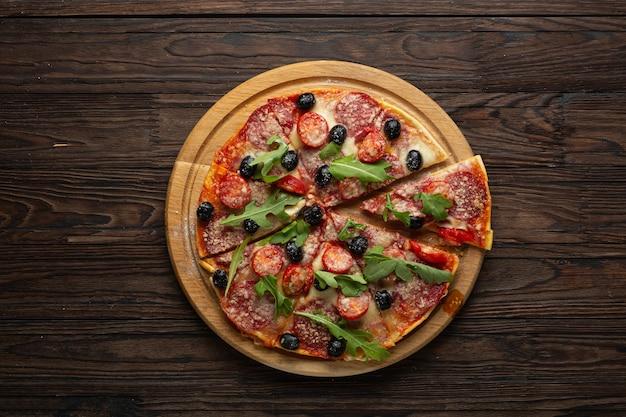Пицца пепперони на деревянной доске вид сверху