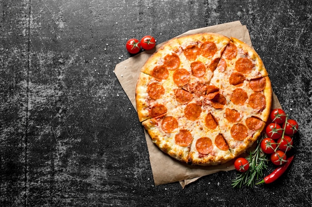 Pepperoni pizza on paper with tomatoes and rosemary.