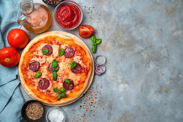 페퍼로니 피자, 토마토, 토마토 소스, 양파, 올리브 오일, 향신료 회색 배경에. 요리, 신선한 베이킹의 개념.