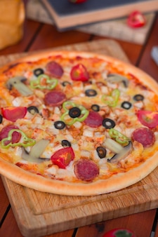 Pepperoni pizza with bell pepper, tomato slices, mushroom and olives.
