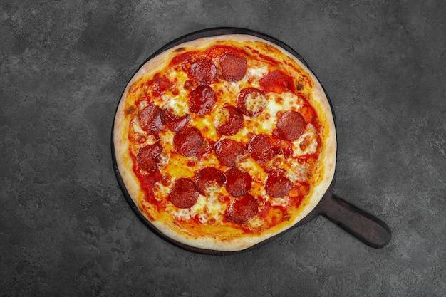 Пицца пепперони с помидорами черри, сыром на черном фоне