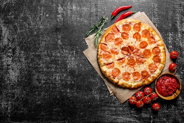 Pepperoni pizza with chili, rosemary and tomatoes on dark wooden table