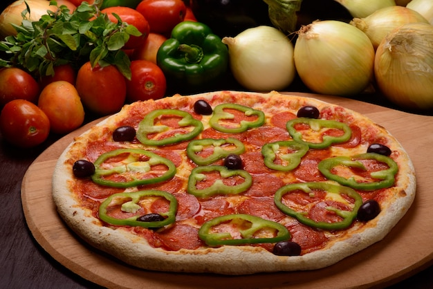 Pepperoni pizza with green peppers on wooden board and vegetables in the background.