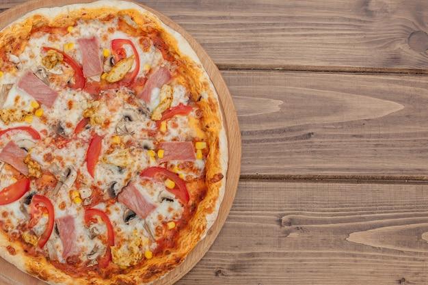 Pepperoni pizza with mozzarella cheese, ham, tomatoes, pepper, spices . italian pizza.