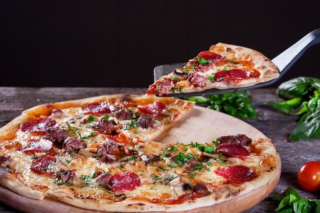 木製の背景にサラミマッシュルームミートビーフチーズとネギとペパロニピザ