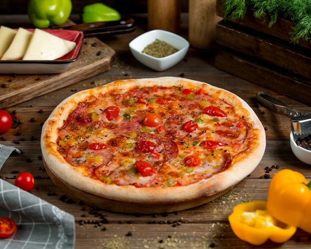 Pepperoni pizza with tomato bell peppers herbs and cheese