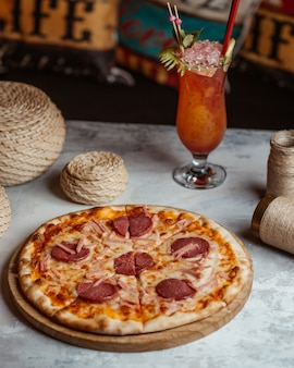 Pepperoni pizza on a wooden board with a glass of cocktail.
