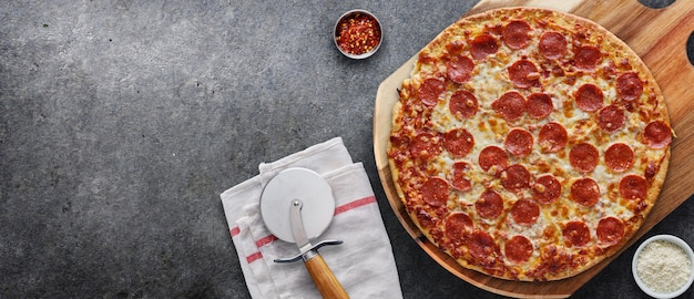Pepperoni pizza on wooden serving board shot top down with copy space composition