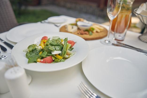 Перец и помидор с зеленым салатом стоя за обеденным столом