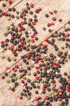 Перец острый, красный, черный, белый и зеленый перец на деревянных фоне.
