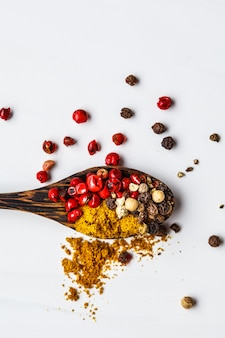 Peppers and spices on wooden spoon, white background.