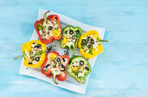 Peppers stuffed with rice and cheese vegetarian food wooden background top view