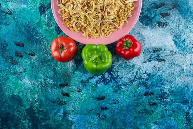 青いテーブルの上に、皿にピーマン、トマト、麺。