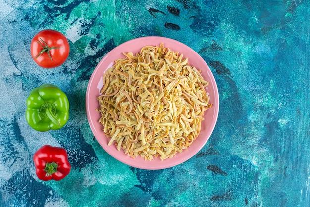 Peperoni, pomodori e noodle in un piatto, sul tavolo blu.