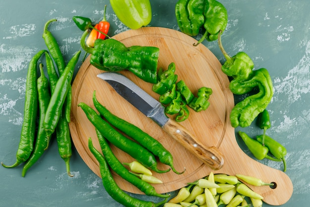 Peppers with knife on plaster and cutting board,