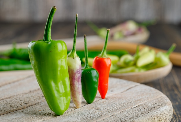 Peppers in wooden spoons on wooden and cutting board.