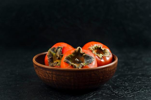 秋の果物。黒い木製の表面にper。粘土板のper。
