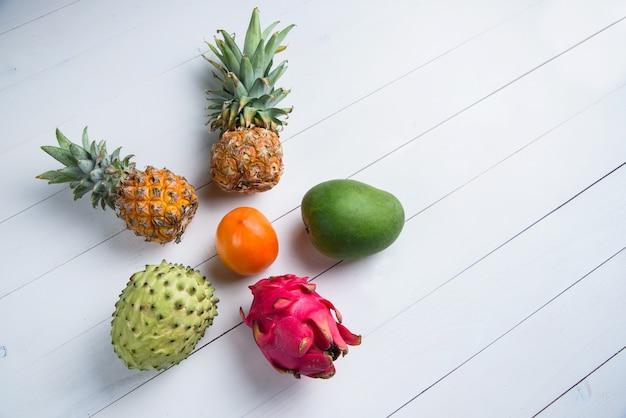 白のエキゾチックな新鮮な夏の果物。ドラゴンフルーツ、パイナップル、per、マンゴー、アノナチェリモラフラットレイアウト無料コピースペース。