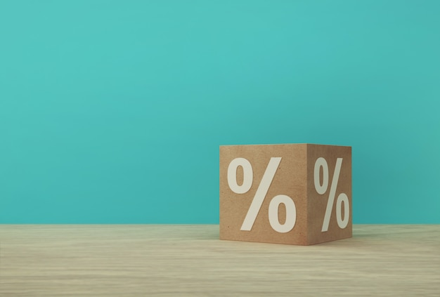 Percentage sign symbol icon with paper cube block on wooden table and blue background.