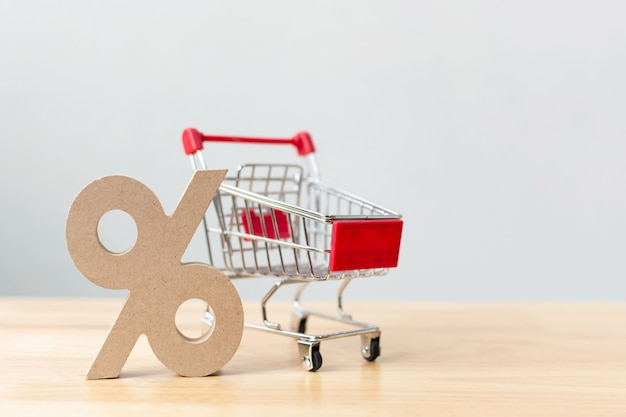 Percentage sign symbol icon wooden and shopping cart on wood table