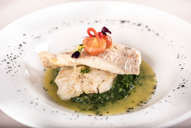 Perch fillet with spinach, sauce and tomato, decorated with eatable flowers and red leaf