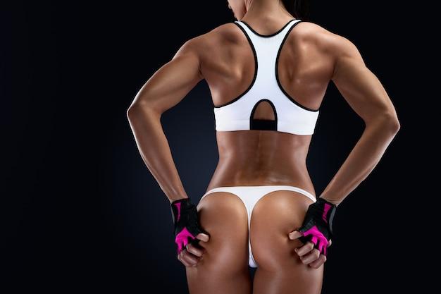 Copyspace와 검은 배경에 여성 운동 선수의 완벽한 복부 근육. 여성 보디빌더는 체육관 운동을 할 준비가 된 장갑을 끼고 돌아섰다. 텍스트 복사 공간이 있는 가로 사진